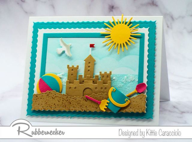 Make a sandcastle beach card with colorful beach toys and a sparkly ocean background  using dies made by Rubbernecker Stamps.