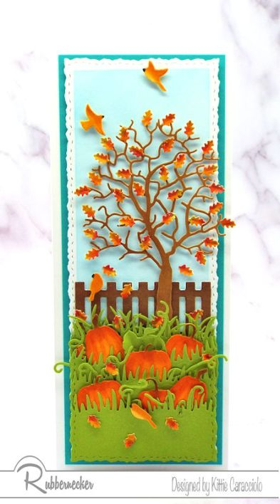 A slimline fall card showing off a die cut tree with shaped paper leaves and hand colored die cut pumpkins
