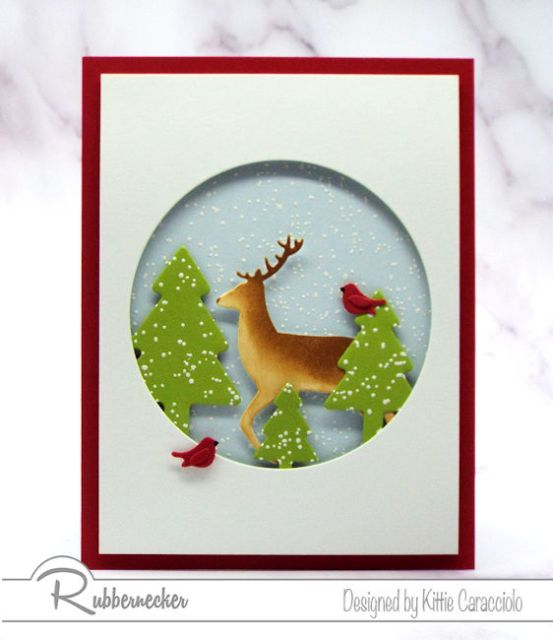 This Snowy Winter Scene with the buck and cardinals posing in the falling snow was made using die cuts from Rubbernecker