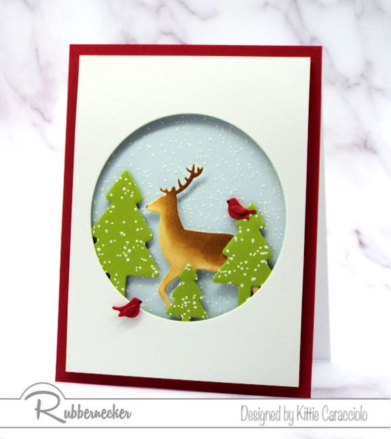 A Snowy Winter Scene on a handmade card using die cuts for the buck, cardinals, pine trees and round window from Rubbernecker