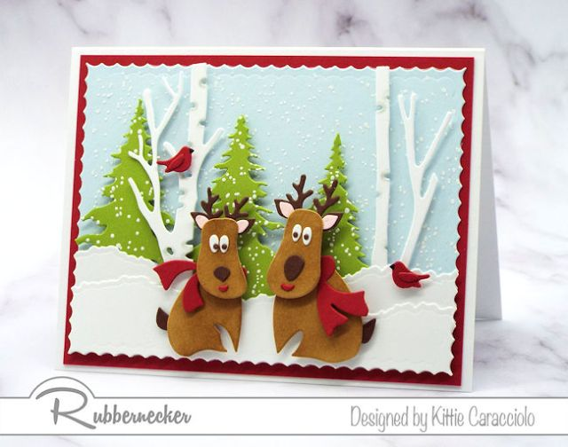 a handmade reindeer card featuring two adorable die cut reindeer and tiny die cut cardinals against a winter background