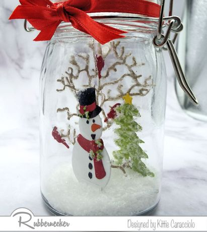 Come learn how to make a snow globe in a mason jar like this one with a die cut snowman, tree and evergreen