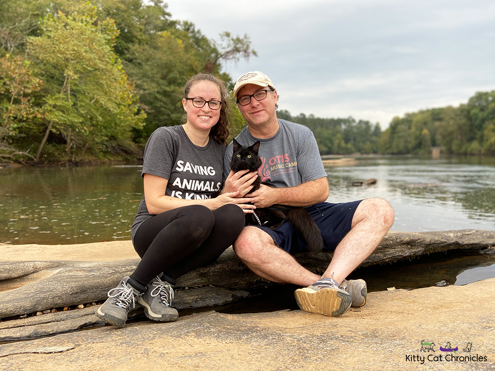 Family photo of a man, woman, and black cat at the Ocmulgee River