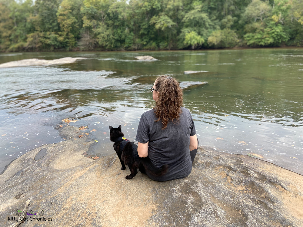 woman and black cat sitting by the Ocmulgee River