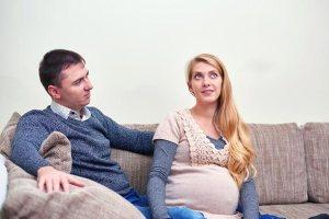 happy-pregnant-couple-sitting-on-sofa