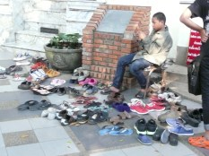 Kid texting amongst the pile of shoes