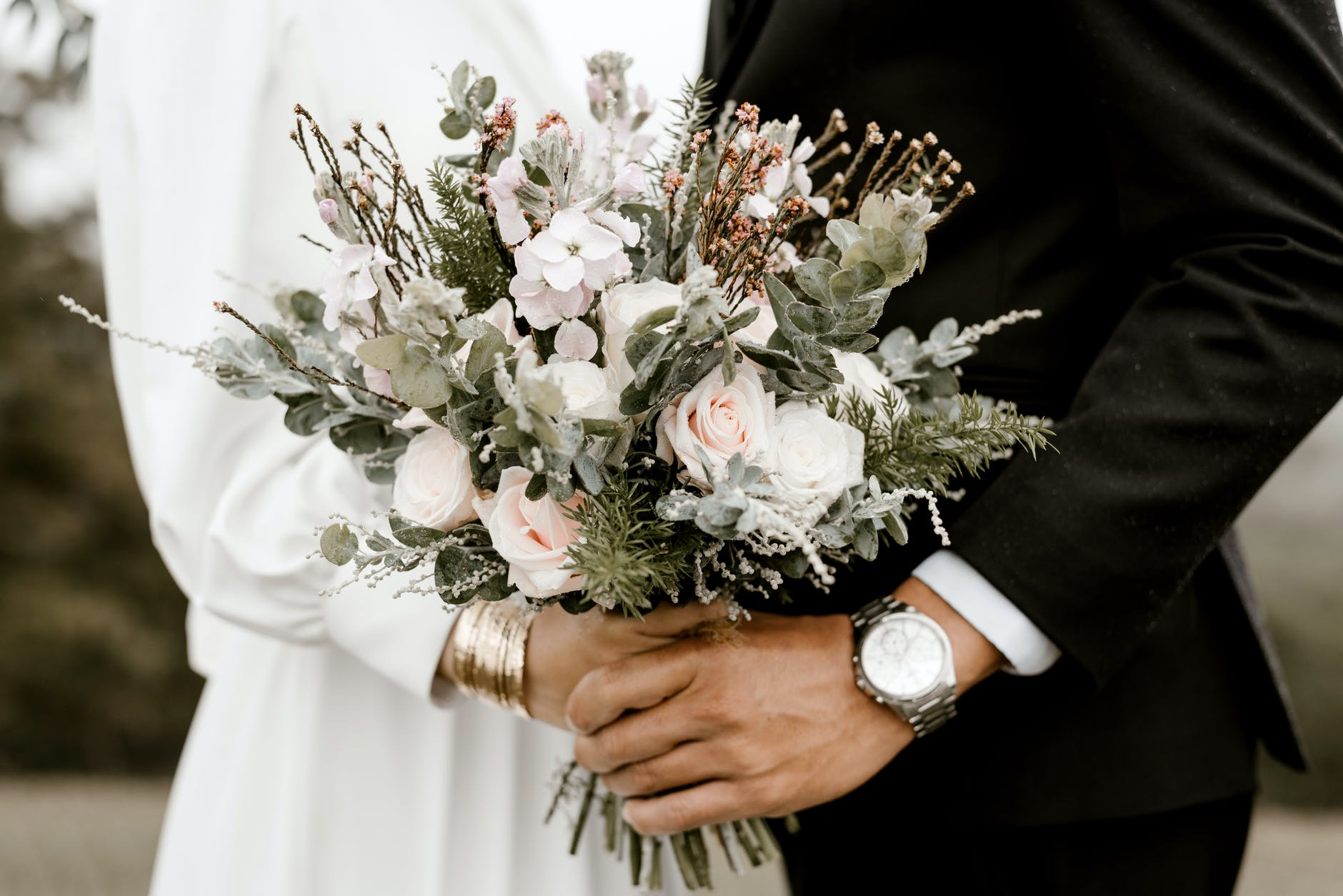 bridge and groom standing while holding flower bouquet