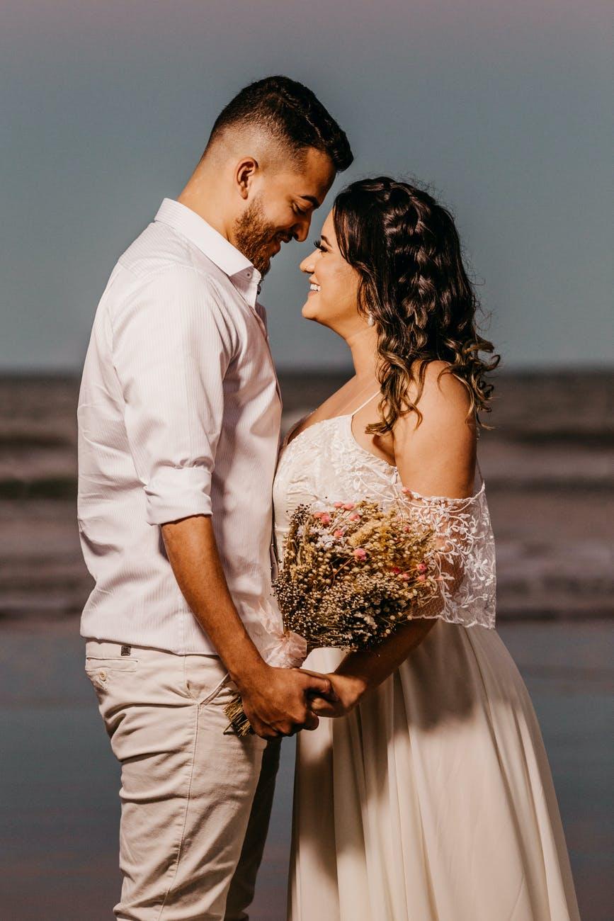 romantic young ethnic newlyweds holding hands on sandy seashore