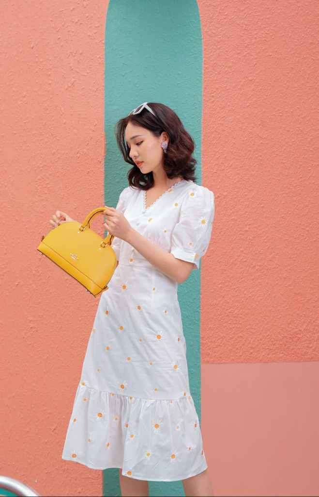 graceful young asian woman standing near bright wall with stylish bag in hand