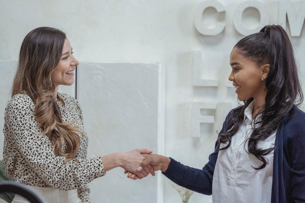two young business women shaking hands