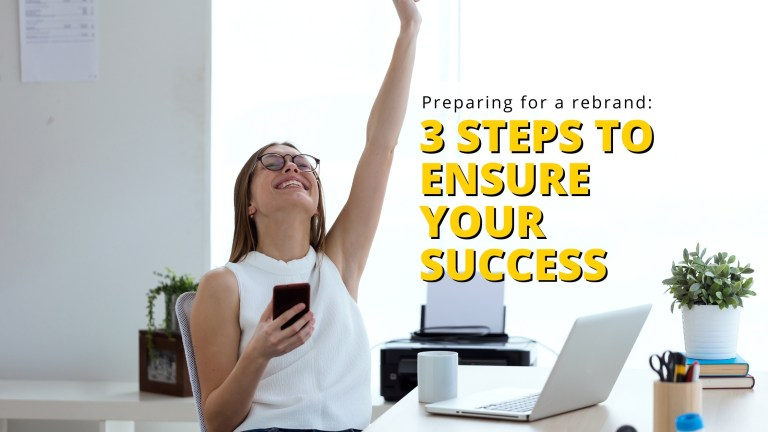 woman in white blouse and glasses with arm in the air smiling while thinking about how to prepare for a rebrand