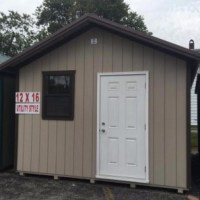 12x16 utility/dog barn. Utterly beige w/ dark brown trim and brown metal roof.