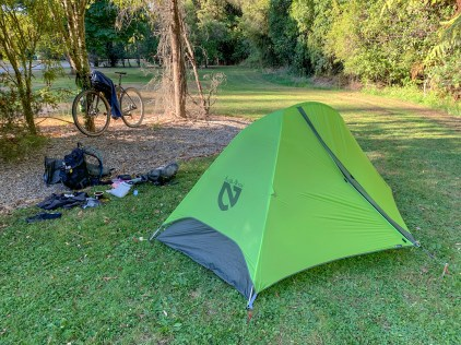tent camping setup in a park, with tent put up and bike and equipment outside the tent