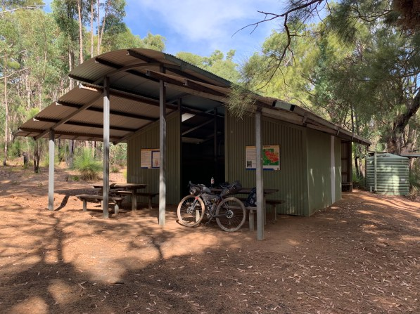 hut structure with picnic tables and water tank
