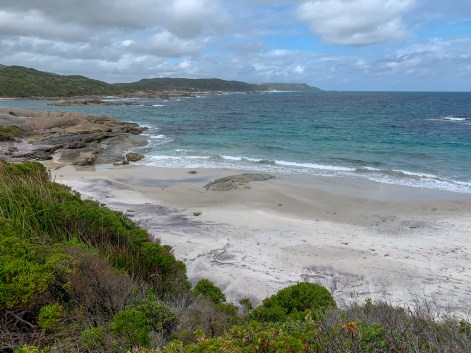 ocean coastline with small waves breaking along a stretch of sandy beach
