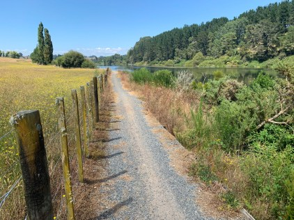 Gravel trail tracing along the edge of a river to the right and a fence to the left