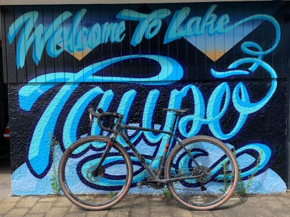 Gravel bike propped against side of a mural, reading 'Welcome to Lake Taupo'
