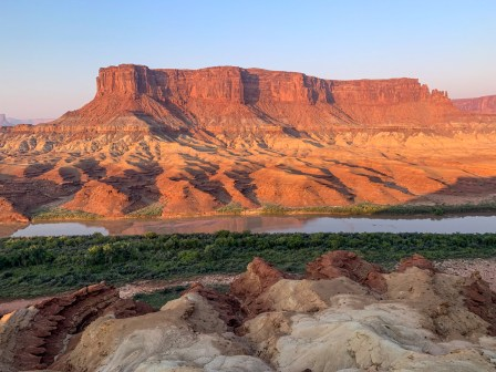 Green River and bank with a butte in the distance in early morning light