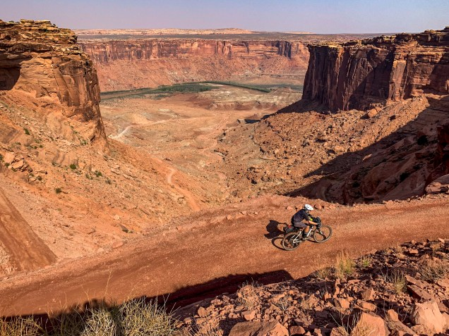 cyclist riding uphill on a dirt road rising from the canyon floor