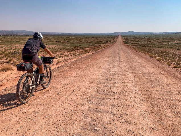 cyclist riding on dirt road stretching into the distance