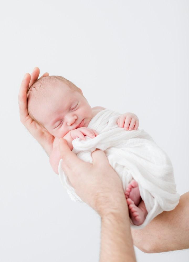 Papa hält Baby Babyfoto Hände Zeitlose Babyfotografie Fotostudio Beilstein