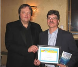 Bruce Haring of JM Norhtern presents Michael Kleiner with his first place award in the Beach Book Festival for Kleiner's memoir. Beyond the Cold: An American's Warm Portrait of Norway