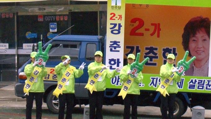 Wahlkampf in Süd-Korea, 5 Wahlhelfer vor einem Werbeplakat auf einem Kleinlaster