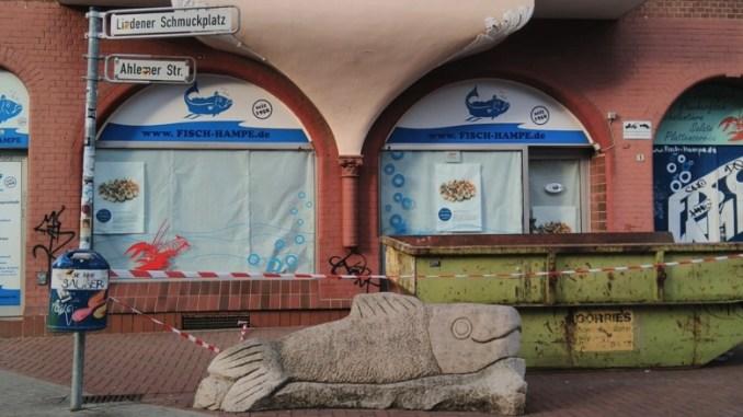 Steinskulptur Fisch vor vor geschlossenem Fisch-Hampe am Schmuckplatz