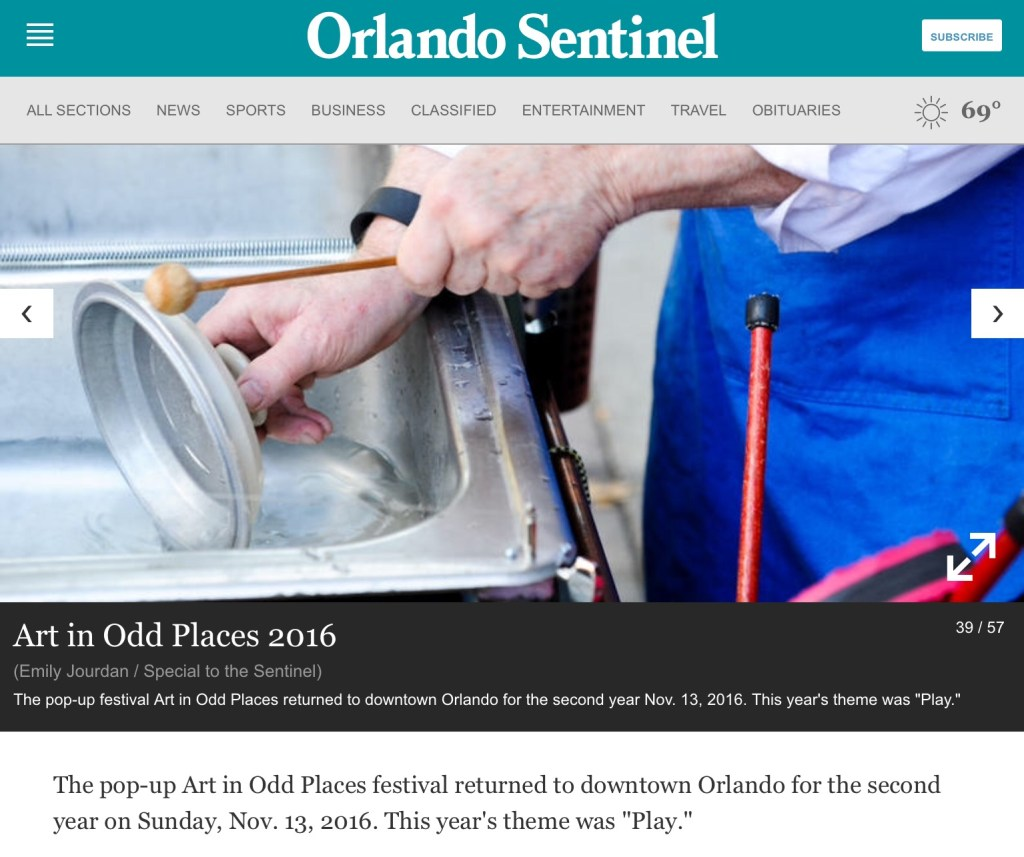 "a photo in the Orlando Sentinel Newspaper of klimchak performing ""When You Whistle, It's Not Work"". He is playing a pan lid while lowering it into water to change the pitch,"