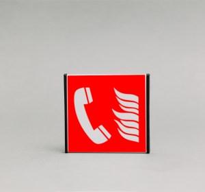 Gaisro avarinio telefono ženklas, kuris yra 93x93mm išmatavimų yra skirtas nurodyti avarinį telefoną kilus gaisrui patalpose.