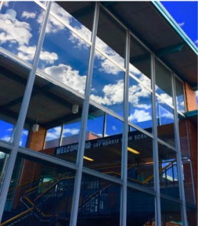 At the school of Loy Norrix, clouds roll over the sky. Looking into the glass of the school you can see a picture. Photo Credit / Jakia Edmonson