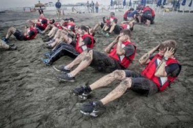 Hombres con chaleco rojo y short negro sentados en la arena haciendo ejercicio