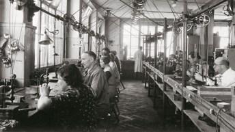 Hombres y mujeres sentados trabajando dentro de una fabrica Montblanc