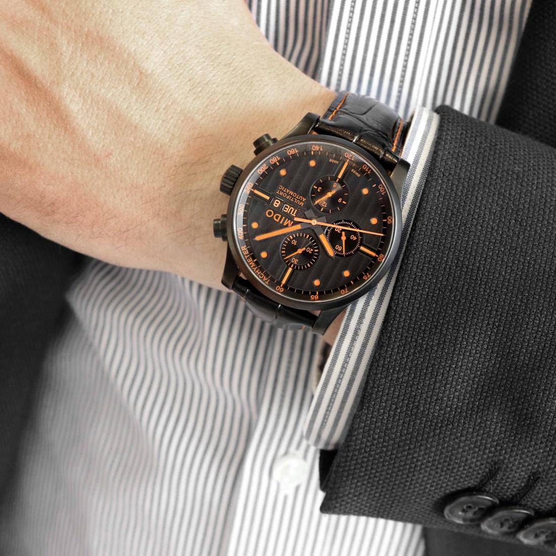 Brazo de un hombre utilizando el reloj MIDO en color negro con detalles naranjas