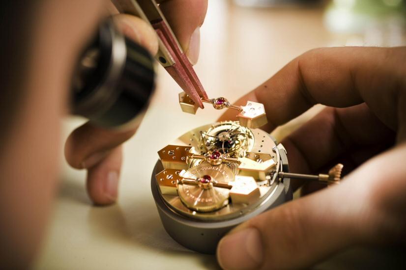 Colocación de una pieza con unas pinzas a una estructura de un reloj