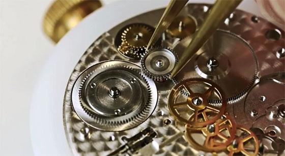 Engranes de un reloj siendo compuestos con unas pinzas