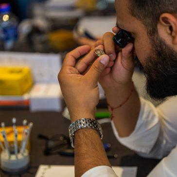 Hombre con una lupa de ojo observando una pieza de reloj
