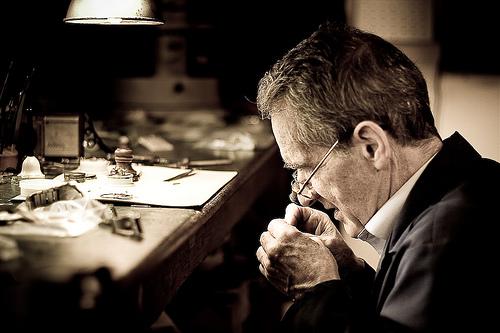 Hombre relojero sentado frente a una mesa con instrumentos para la compostura de relojes