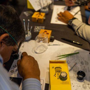 Hombres con hojas blancas haciendo diseños utilizando una pequeña lupa de ojo