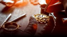 Pieza de un reloj siendo reparada con algunos instrumentos sobre una mesa