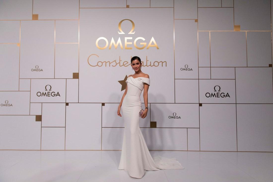Praya Lundberg con vestigo blanco en evento de OMEGA con letras doradas y fondo blanco