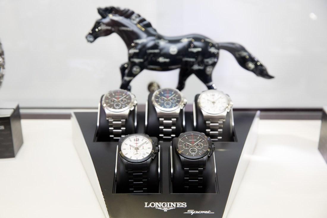Expo de relojes Longines con un caballo de fondo