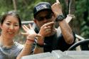 Mujer oriental y hombre con gorra mostrando reloj