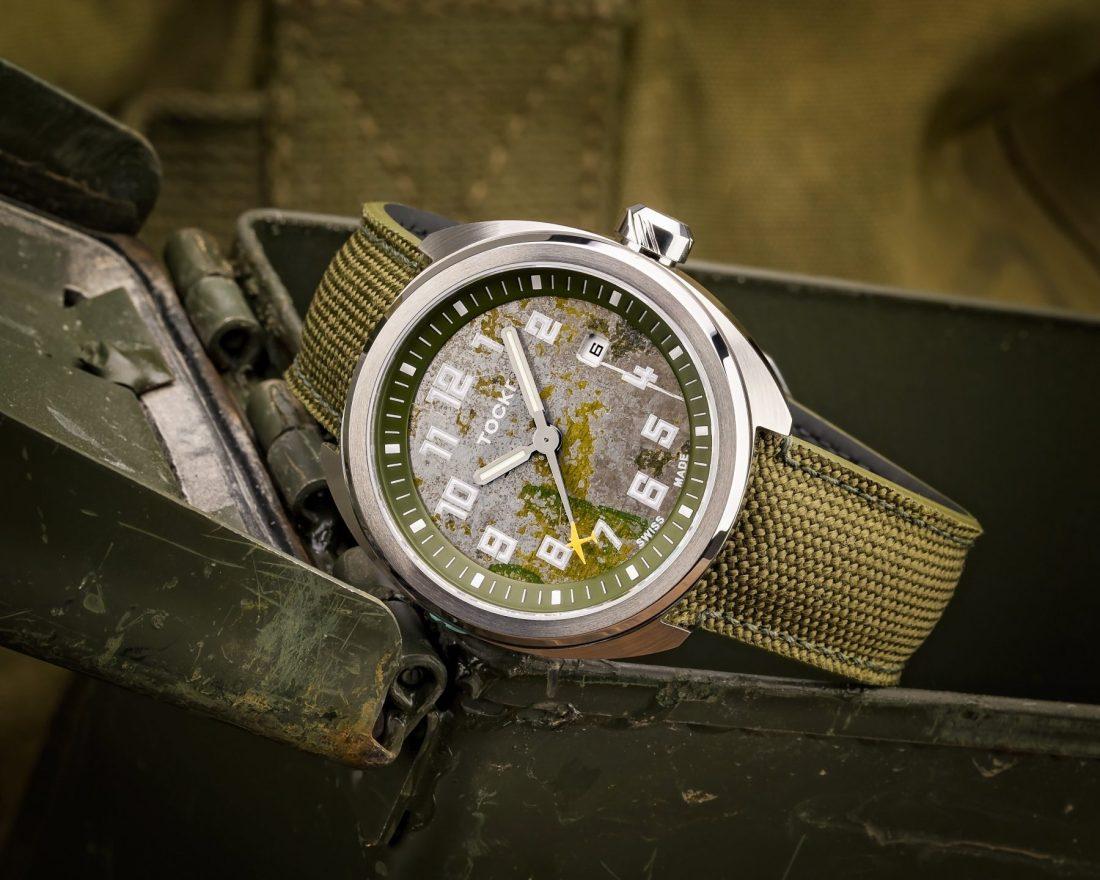 Reloj C-47 sobre una caja de metal y fondo verde