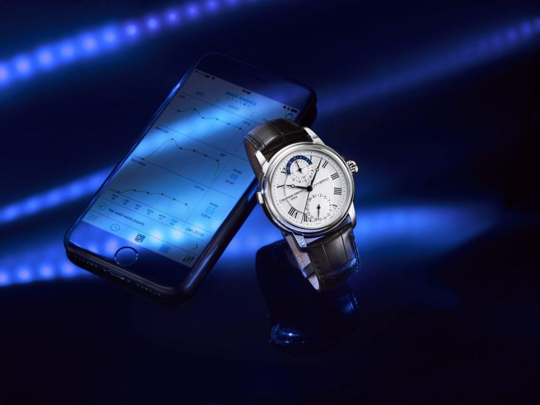 Reloj Frédérique Constant en color negro con detalles en plateado y blanco junto a un celular y fondo azul