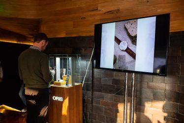 Persona viendo el reloj Oris Artix junto a una pantalla con una imagen del reloj