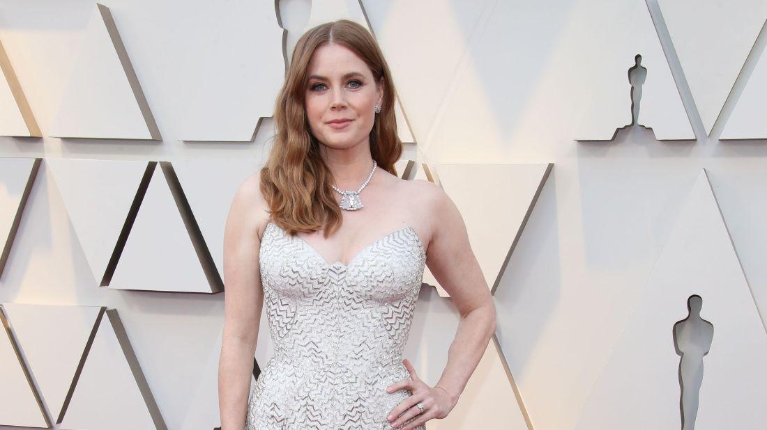 Amy Adams con vestido blanco con aretes y collar con diamantes en blanco y platino
