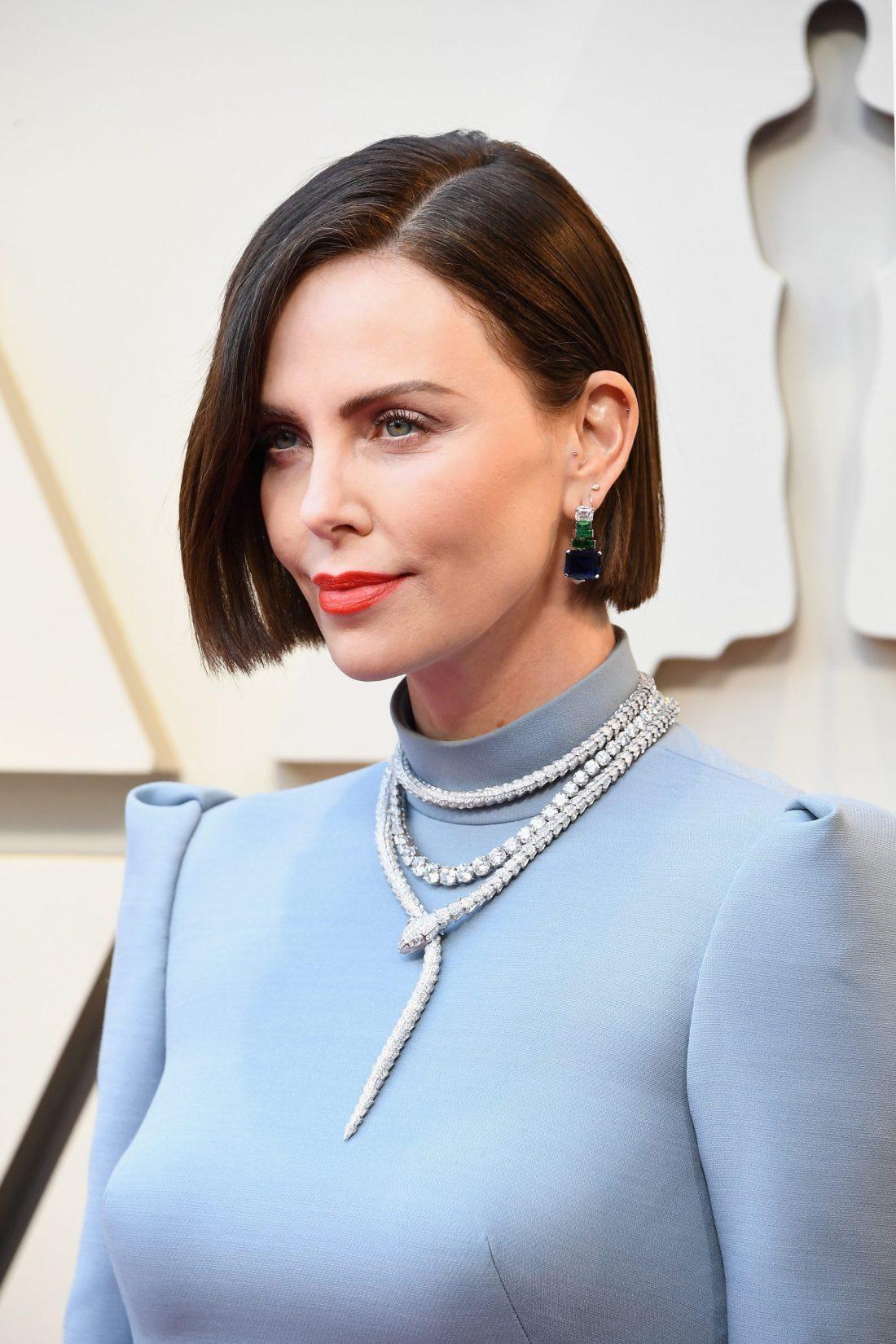 Charlize Theron con vestido azul collar en oro blanco y aretes en color verde con azul