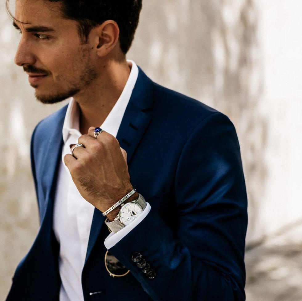 Hombre con saco azul y camisa blanca utilizando un reloj de Filippo Loreti