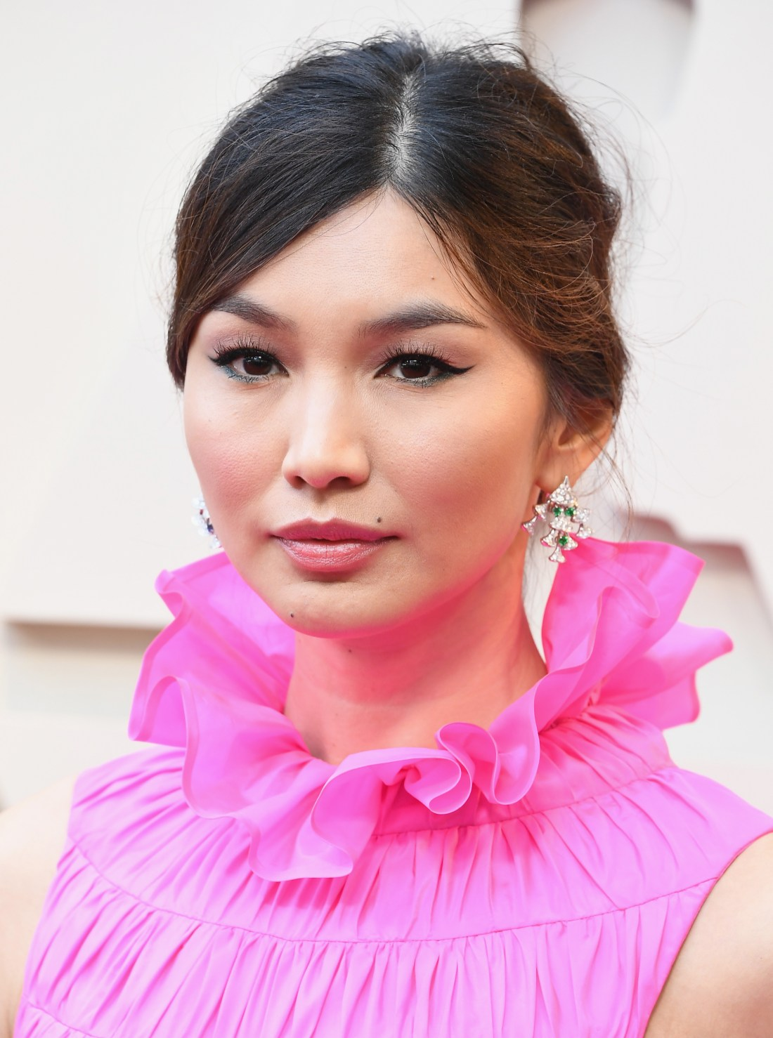 Gemma Chan con vestido en color rosa y aretes con diamantes blancos y verdes